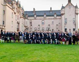 Large group of peopleion Scottish traditional dress pose for a photograph in from of a castle